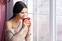 Young woman sitting near window Stock Image