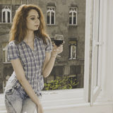 Young woman sitting near window with a glass of wine Stock Photography
