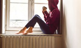Young woman sitting near the window looking outside drinking coffee in a nostalgic mood. Young woman in fitness clothes sitting near the window looking outside royalty free stock photography