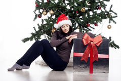 Young woman sitting near xmas tree with present Stock Photo