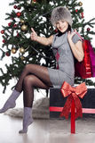 Young woman sitting near xmas tree with present after shopping d Royalty Free Stock Image