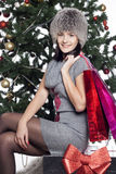 Young woman sitting near xmas tree with present after shopping d Royalty Free Stock Photography