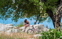 Young woman sitting nearby the bicycle. Young woman sitting on the stone nearby the bicycle Royalty Free Stock Photography