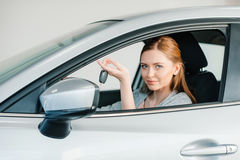 Young woman sitting in new car and holding key Royalty Free Stock Image