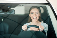 Young woman sitting in new car and looking at camera Stock Image