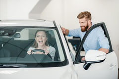 Young woman sitting in new car and man standing near Royalty Free Stock Photo