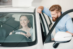 Young woman sitting in new car and man standing near Stock Image