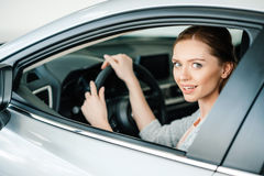 Young woman sitting in new car and smiling at camera Stock Photography