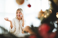 Young woman sitting next to a Christmas tree, talking over phone Royalty Free Stock Photography