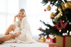 Young woman sitting next to a Christmas tree, talking over the phone Royalty Free Stock Image