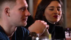 Young woman sitting next to a man, sipping on a cocktail and looking at him. Brunette woman with red lipstick sipping on a pink cocktail, looking and smiling at stock video
