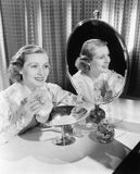 Young woman sitting next to mirror and holding a powder puff Stock Image