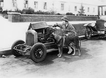 Young woman sitting next to small car looking at the engine with her German shepherd stock image