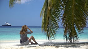 Young woman sitting by the ocean under a palm. Young woman sitting by the ocean under a palm tree stock video
