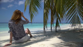 Young woman sitting by the ocean under a palm. Young woman sitting by the ocean under a palm tree stock footage