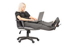 Young woman sitting on office chair with her legs up and working Stock Photos