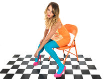 Young Woman Sitting on an Office Chair. Isolated white background wearing an orange dress and blue tights with pink shoes Stock Photos