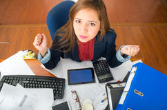 Young woman sitting by office desk with supplies spread out, interacting looking into camera as seen from above angle Royalty Free Stock Photo