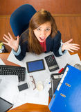 Young woman sitting by office desk with supplies spread out, interacting looking into camera as seen from above angle Stock Photos