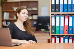 Young woman sitting in office room Royalty Free Stock Photography
