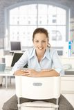 Young woman sitting in office smiling Royalty Free Stock Image