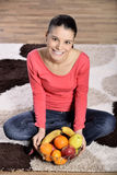 Young Woman Sitting On Carpet And Enjoying Fruits Royalty Free Stock Image
