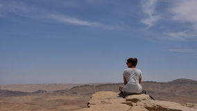 Young Woman Sitting On Cliff`s Edge And Looking At The Desert