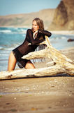 Young Woman Sitting On The Log On The Beach Royalty Free Stock Image