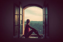 Young woman sitting in an open old window looking on the landscape of Tuscany, Italy. Royalty Free Stock Images