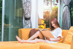 Young woman sitting at opened window reading a book enjoys of re stock images