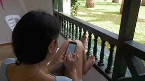 Young woman sitting on outdoor balcony and using mobile phone. Woman texting message on phone. Shoulders view high angle. Young woman sitting on outdoor balcony stock video footage