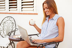 Young Woman Sitting Outdoors With Laptop And Drinking Coffee Royalty Free Stock Photography