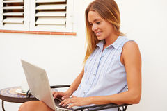 Young Woman Sitting Outdoors With Laptop And Drinking Coffee Stock Photography