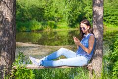 Young woman sitting outdoors and looking at the Royalty Free Stock Images