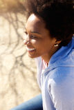 Young woman sitting outdoors and smiling. Close up portrait of happy young african woman sitting outdoors and smiling Stock Photos