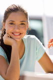 Young woman sitting outdoors, smiling, portrait Stock Photos