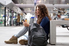 Young woman sitting outdoors using mobile phone Stock Photography
