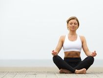 Young woman sitting outdoors in yoga pose. Beautiful young woman sitting outdoors in yoga pose Royalty Free Stock Photography