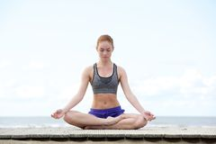 Young woman sitting outdoors in yoga position Royalty Free Stock Photography