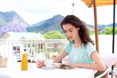 Young woman sitting outside with coffee and book Royalty Free Stock Photos