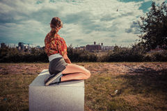Young woman sitting outside and looking at city Royalty Free Stock Image