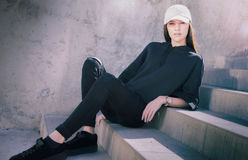 Young woman sitting outside on steps wearing cool fashionable clothing Royalty Free Stock Photos