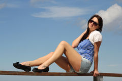 Young woman sitting over blue sky Stock Image