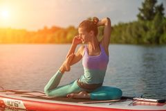 Young woman sitting on paddle board, practicing yoga pose. Doing yoga exercise on sup board, active summer rest. Exercise for flexibility and stretching of royalty free stock images