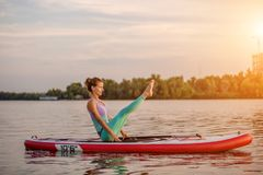Young woman sitting on paddle board, practicing yoga pose. Doing yoga exercise on sup board, active summer rest. Exercise for flexibility and stretching of stock images