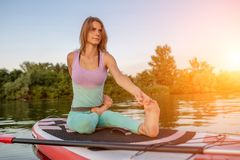 Young woman sitting on paddle board, practicing yoga pose. Doing yoga exercise on sup board, active summer rest. Exercise for flexibility and stretching of royalty free stock photo