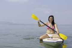 Young woman sitting on a paddle board Stock Image