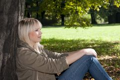 Young woman sitting in the park Royalty Free Stock Photography