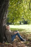 Young woman sitting in the park Stock Photo
