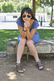 Young woman sitting on a park bench Stock Photo